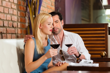 Attractive young couple drinking red wine in restaurant or bar, it might be the first date Stock Photo - 15785034
