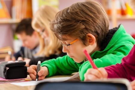 ni�os pensando: Educaci�n - Los alumnos de la escuela primaria o elemental hacer los deberes o tener una prueba escolar