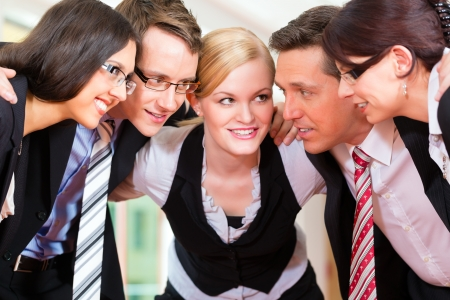 team spirit: Business - group of businesspeople standing in office, they seem to be a very good team, business metaphor Stock Photo