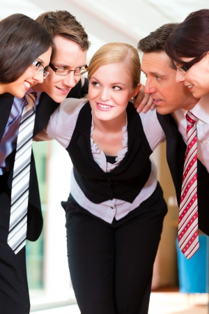 Business - group of businesspeople standing in office, they seem to be a very good team, business metaphor photo