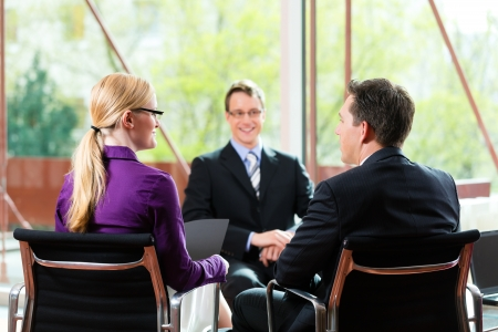 Business - young man as applicant sitting in job interview with future boss and HR photo