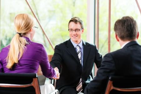 interview job: Negocios - joven sentado como candidato en la entrevista de trabajo con el jefe de futuro y de recursos humanos