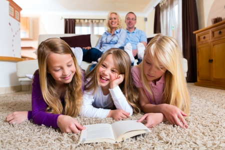 multiple family: Family reading a book together at home in their living room Stock Photo