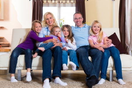sibling: Family, father, mother and four sisters sitting on a couch in their living room Stock Photo