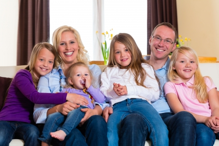 man couch: Family, father, mother and four sisters sitting on a couch in their living room Stock Photo