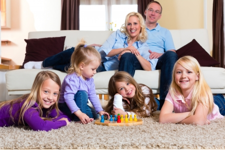 multiple family: Family playing board game ludo at home on the floor Stock Photo