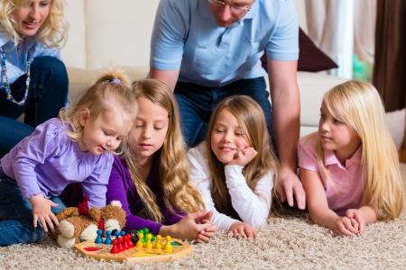 mother board: Family playing board game ludo at home on the floor Stock Photo