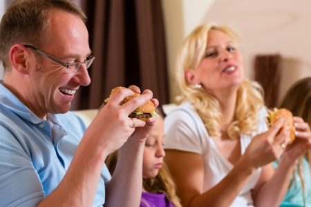 Young family - mother, father and daughters - is eating hamburger or fast food at home photo
