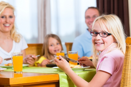 Family eating lunch or dinner and sitting at the table photo