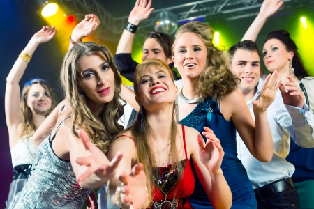 discotheque: Young people dancing in club or disco and have party; the girls and boys, friends, having fun