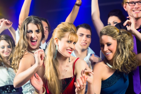 Young people dancing in club or disco and have party; the girls and boys, friends, having fun photo