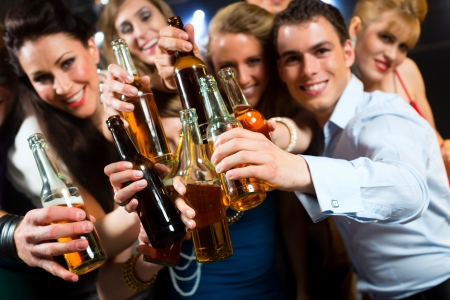 after the party: Young people in club or bar drinking beer out of a beer bottle and have fun