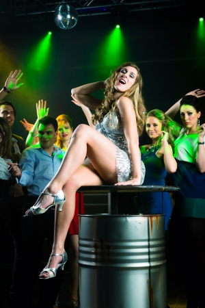 Young people dancing in club or disco and have party, the girls and boys, friends, having fun Stock Photo - 15784973
