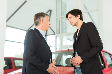 sell car: Mature single man with red auto in light car dealership with a male customer, a young man, he is obviously buying a car or is a car dealer