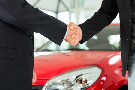 sell: Two men in business suits shaking hands after a successful car purchase