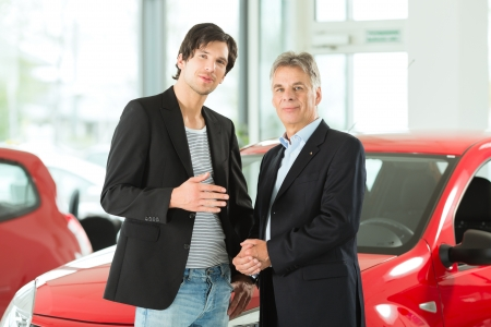 selling service: Mature single man with red auto in light car dealership with a male customer, a young man, he is obviously buying a car or is a car dealer