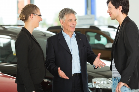 sell car: Mature single man with autos in light car dealership with a young couple, he obviously is buying a car or is a car dealer Stock Photo