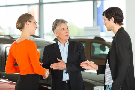 car dealer: Mature single man with autos, handshaking in light car dealership with a young couple, he obviously is buying a car or is a car dealer  Stock Photo