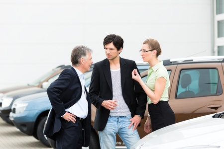 Mature man and young couple standing on a parking place standing in the middle of cars, obviously they are in a sales pitch photo