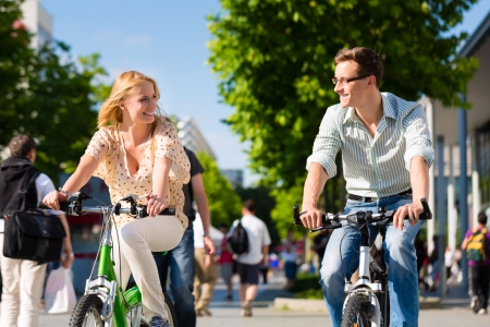 city bike: Couple - man and woman - riding their bikes or bicycles in their free time and having fun on a sunny summer day