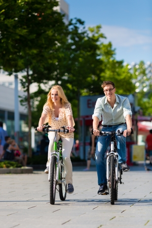free riding: Couple - man and woman - riding their bikes or bicycles in their free time and having fun on a sunny summer day