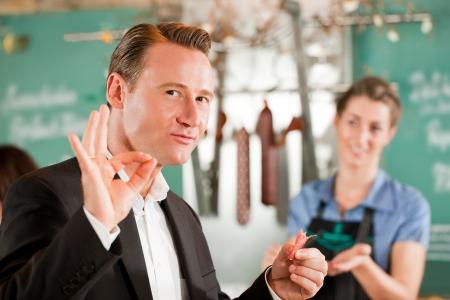 butcher shop: Satisfied customer showing positive sign at butcher shop