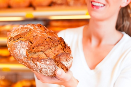 Female baker or saleswoman in her bakery with fresh pastries and bakery products photo