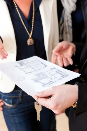 accommodation broker: Young realtor explain ground plan to couple in an apartment