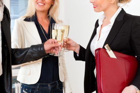 Real estate market - young couple looking for real estate to rent or buy, they celebrate with champagne and clinking glasses Stock Photo - 16011602