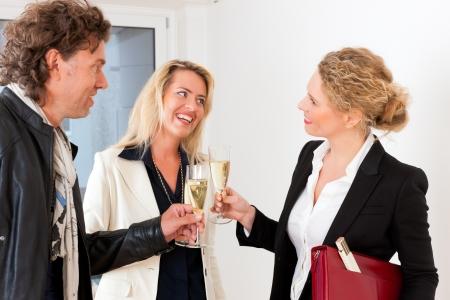 clinking: El mercado inmobiliario - pareja joven en busca de bienes inmuebles para alquilar o comprar, celebrar con copas de champ�n y tintineo
