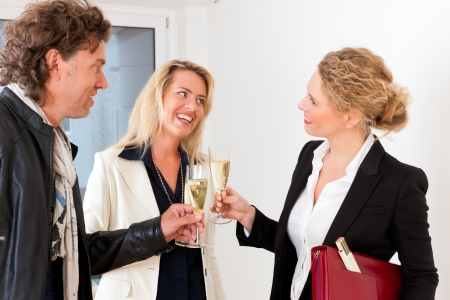 accommodation broker: Real estate market - young couple looking for real estate to rent or buy, they celebrate with champagne and clinking glasses