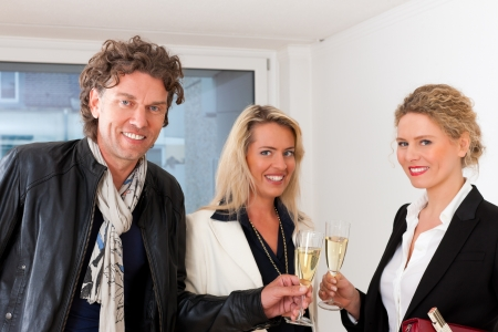 tenant: Real estate market - young couple looking for real estate to rent or buy, they celebrate with champagne and clinking glasses