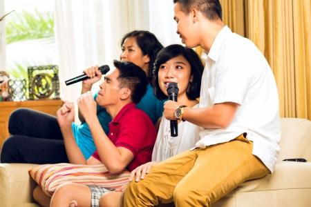 people singing: Asian people singing at karaoke party and having fun