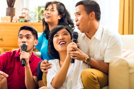 Asian people singing at karaoke party and having fun photo
