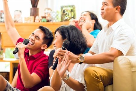 personas cantando: Los asi�ticos cantando en la fiesta de karaoke y divertirse Foto de archivo
