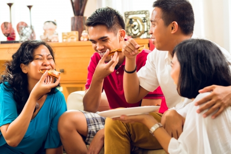 Asian people eating pizza at party or dinner and smiling