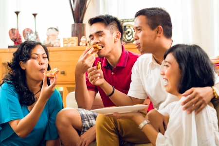 Asian people eating pizza at party or dinner and smiling photo
