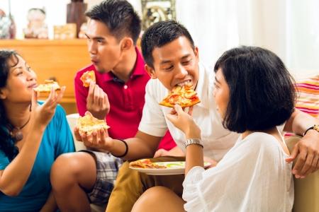 hombre comiendo: Los asi�ticos comiendo pizza en la fiesta o cena y sonriente