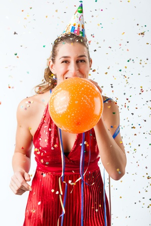 Woman celebrating birthday at a shower of confetti with balloon and smiling photo