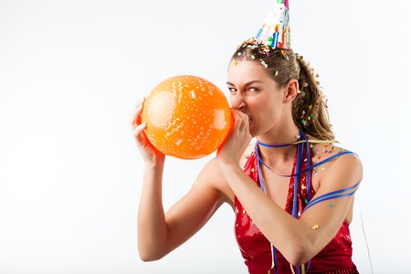 Woman celebrating birthday blowing up a balloon at shower of confetti