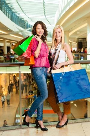 centro comercial: Dos amigos femeninos con bolsas de la compra que se divierten mientras que las compras en un centro comercial