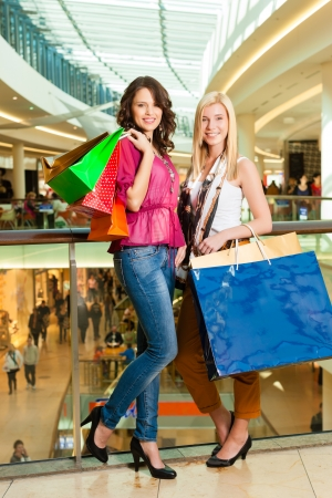 Two female friends with shopping bags having fun while shopping in a mall photo