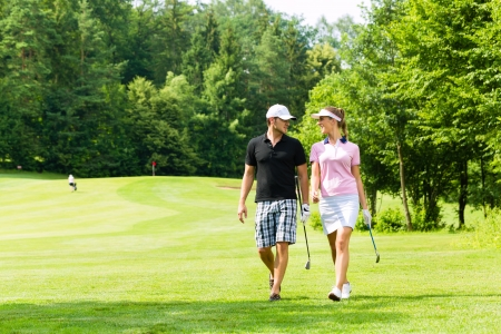 woman golf: Young sportive couple playing golf on a golf course, they walking to the next hole