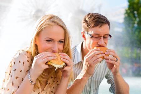 Paar ist hungrig und essen einen Burger zum Mittagessen in der Sonne