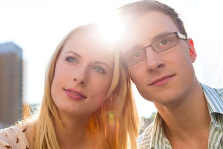 Couple looking dreamily into the sky and is happy to be together photo