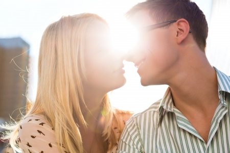 tangible: Couple sitting in the sun and kisses because happiness is tangible