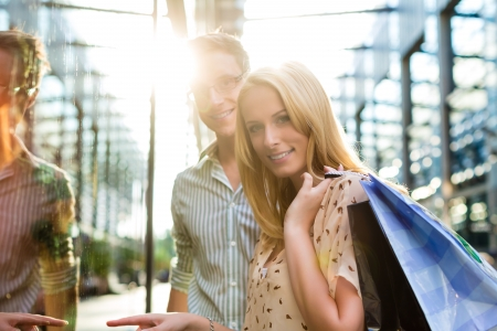 long weekend: Couple shopping in the free time in the sun with shopping bag Stock Photo