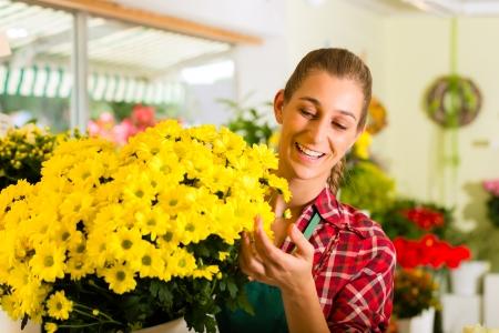 petites fleurs: Femme fleuriste boutique de fleurs en p�pini�re ou pr�sentant des fleurs