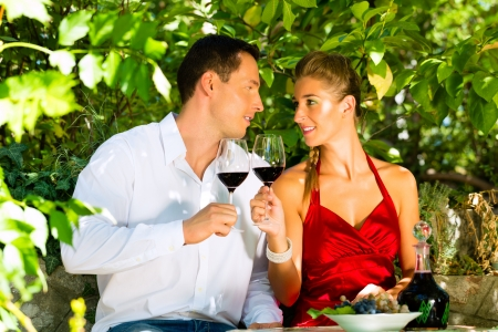 romantically: Woman and man sitting romantically under grapevine and drinking wine from a glass