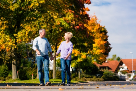 strolling: Man and woman, senior couple, having a walk in autumn or fall outdoors, the trees show colorful foliage